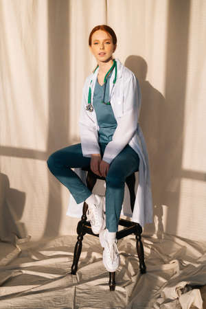 Portrait of serious sensual female doctor in white coat sitting on chair near window in sunny day in medical clinic office. Young redhead woman surgeon posing with stethoscope looking at camera. Stock Photo