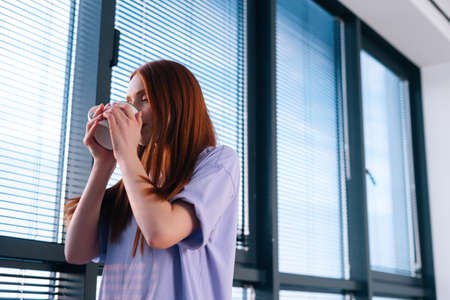Close-up of charming confident redhead young woman drinking coffee from mug and looking through the window on cityscape. Calm lady watching sunset near panoramic window having rest with cup of tea.