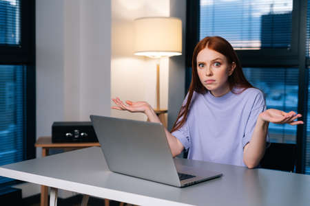 Frustrated young woman confused by laptop computer problem sitting at desk in home office near window evening at late, looking at camera. Bewildered female spreads hands incomprehensibly.