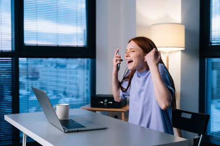 Happy surprised young woman getting good online news on mobile phone sitting at desk in office near window. Shocked amazed redhead female face enjoying success using smartphone at home late in evening
