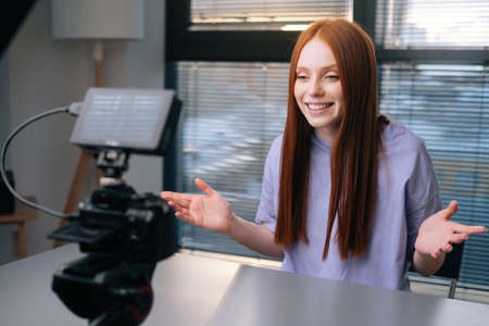 Side view of cheerful young woman blogger turns on camera, waving hand in greeting and starts talking looking into camera. Smiling redhead female record commercial online video course at home office. Stock Photo