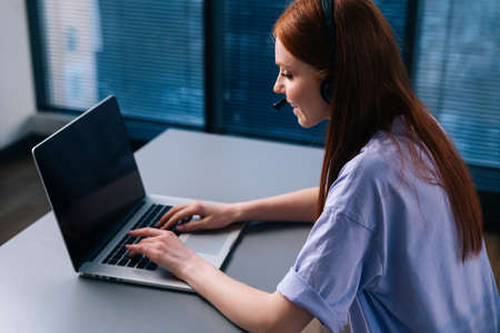Back top view of young woman operator using headset and laptop during customer support at home office. Young redhead female student communicating online by video call on background of window. Stock Photo