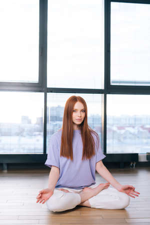 Serene attractive young woman meditating sitting on floor in lotus pose on background of window in light office room. Calm redhead lady relaxation during yoga workout at home looking at camera.