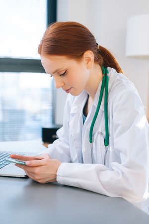 Close-up side view of positive female doctor in white coat typing message on phone, sitting at desk with laptop near window in sunny day. Focused woman physician giving remote diagnose to patient. Stock Photo