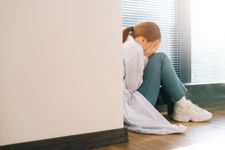 Close-up back view of sad depressed female doctor crying sitting near window holding head and arms on knee. Frustrated upset young woman physician feeling worried about professional malpractice.