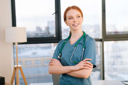 Portrait of happy female doctor in blue green uniform standing arms crossed near window in sunny day in medical clinic office. Redhead woman surgeon posing with stethoscope looking away. Stock Photo