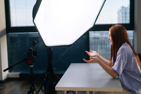 Side view of successful young woman blogger recording video vlog using professional camera and softbox sitting at desk on background of window. Happy redhead female having online conference in office.