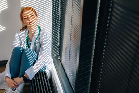 Close-up of depressed sad young female doctor in white coat sitting on floor hugging legs with hands near window. Unhappy woman physician depression feeling worried about professional malpractice. Stock Photo
