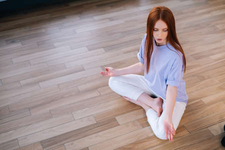 Top view of redhead peaceful young woman meditating sitting on floor in lotus pose in light office room. Calm pretty redhead lady relaxation during yoga workout at home with closed eyes.