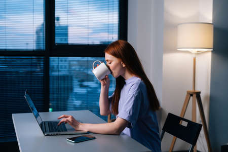 Cheerful redhead young business woman typing on laptop sitting at desk in dark office and drinking coffee from mug. Happy businesswoman working on computer sitting at desk near window late in evening.
