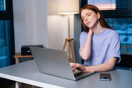 Overworked redhead young woman typing on laptop actively feeling pain in wrist sitting at desk near window in evening. Lady working on laptop and suffering from pain in hand, carpal tunnel syndrome.