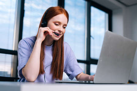 Close-up face of smiling young woman operator using headset and laptop during customer support at home office. Young female student communicating online by video call on background of window.