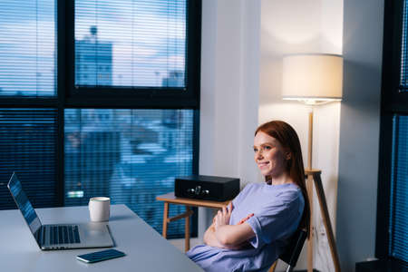 Happy redhead young woman blogger satisfied with completing article in time finishing remote job late at night. Smiling female journalist working sitting at desk near window late in the evening.