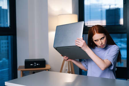 Frustrated young woman confused by laptop computer problem sitting at desk in home office near window evening at late. Unhappy female freelancer holding broken laptop in hand.