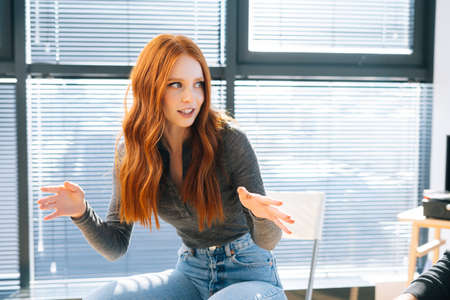 Close-up of attractive young redhead businesswoman talking and discussing new ideas with creative business team, during brainstorming of start-up projects in modern office room near window.