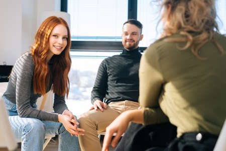 Business team having brainstorming meeting to plan and achieve goal in modern office near window. Young cheerful coworkers sitting on chairs in circle, discussing working or personal issues together.