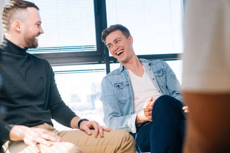 Laughing young business man talking and discussing new ideas with creative business team, during brainstorming of start-up projects in modern office room near window. Stock Photo