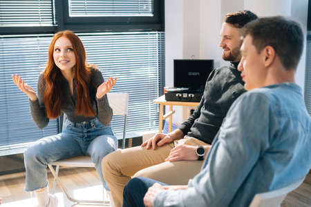 Middle shot portrait of cheerful young redhead businesswoman talking and discussing new ideas with creative business team, during brainstorming of start-up projects in modern office room near window.