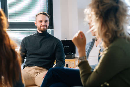Male trainer conduct corporate training with creative business team sitting in circle on chair on background of window. Businessman talking during team-building seminar in modern office room.
