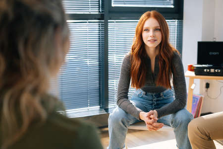 Portrait of young attractive red-haired woman listening to co-workers during brainstorming of start-up projects. Businessman talking during team-building seminar in modern office room. Stock Photo