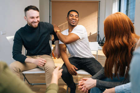 Laughing African American male leader explaining new strategies to young creative business team, during brainstorming in meeting room. Businessman discussing work with team in boardroom.