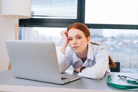 Close-up portrait of tired exhausted young female doctor in white coat sitting at desk with laptop. Front view of overworked woman physician in hospital office looking at camera.
