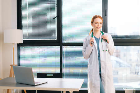 Portrait of pretty female doctor in white coat standing on background of window in sunny day in light medical clinic office. Young redhead woman physician posing with stethoscope looking at camera. Stock Photo