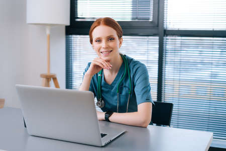 Portrait of attractive smiling young female doctor in blue green medical uniform sitting at desk with laptop on background of window in hospital office of medic clinic, looking at camera.