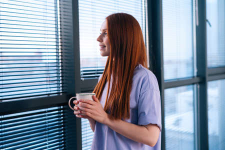 Happy redhead young woman drinking coffee and watching on sunset through the window after working day. smiling lady having rest with cup of tea. Dreaming female drinking warm tea. Stock Photo