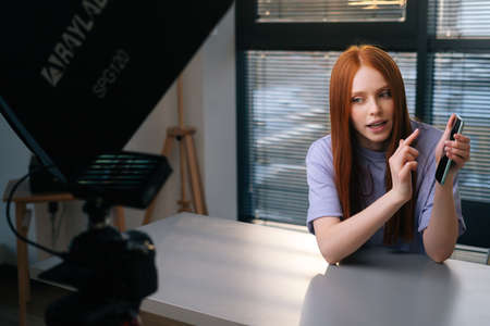 Webcam view of smiling young woman blogger greeting followers and talking about phone during video chat on background of window. POV of cheerful redhead female having presentation during sundown.