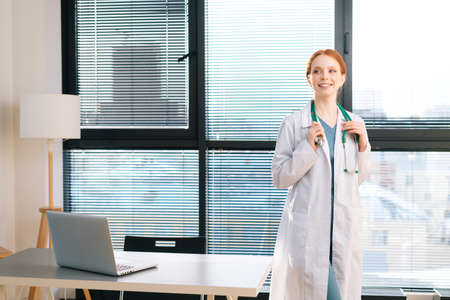 Portrait of friendly female doctor in white coat standing on background of window in sunny day in light medical clinic office. Young redhead woman physician posing with stethoscope looking away.