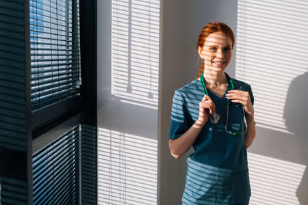 Portrait of positive female doctor in blue green uniform standing near window in sunny day in medical clinic office. Young pretty redhead woman surgeon posing with stethoscope looking at camera.
