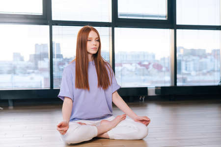 Relaxed attractive young woman meditating sitting on floor in lotus pose on background of window in light office room. Calm redhead lady relaxation during yoga workout at home looking away.