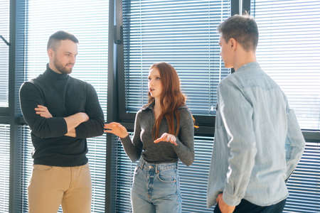 Front view of young redhead businesswoman leader having conversation with male colleagues in modern office room near window. Subordinate office workers listen intently to boss instructions.