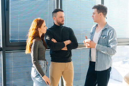 Middle shot portrait of three serious young business people having fun conversation during coffee break in modern office. Confident coworkers enjoy pleasant communication, discuss project by window. Stock fotó