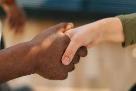 Close-up top view of handshake of Caucasian woman and black male indoors at home office, selective focus. Concept of handshaking black and white hand, interracial friendship and cooperation.