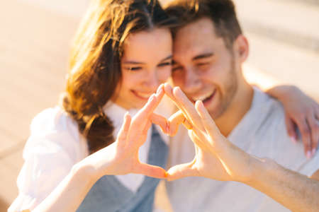 Close-up of happiness young couple making heart with hands resting in city park in summer sunny day. Relationships happy boyfriend and girlfriend enjoying spending time together outdoors. Stock fotó