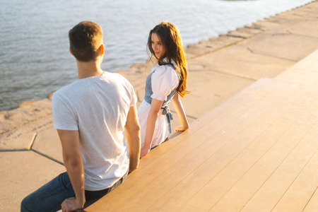 Top side view of young attractive woman flirting with man sitting on bench on city waterfront near river in sunny summer day. Flirty smiling lady and guy looking at each other, love at first sight.