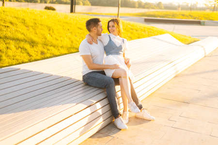Cheerful boyfriend and girlfriend enjoying time together hugging and relaxing sitting on bench in summer sunny day. Happy Caucasian couple in love having romantic walk outdoors enjoying time together.