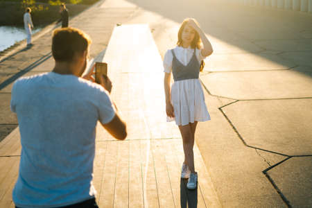 Back view of young man taking picture of girlfriend on mobile phone at sunset near river on city park. Happy attractive Caucasian lady posing for male photographer on background of bright sunbeam Stock fotó