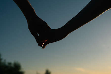 Close-up arms of loving young couple hand-holding and walking towards sunset on background of cloudless sky in evening. Couple in love having romantic walk outdoors enjoying time together.