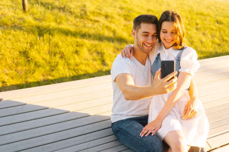 Happy young couple hugging and sharing media in smartphone sitting relaxed on bench in city park on bench in summer sunny day. Caucasian couple having romantic walk outdoors enjoying time together.