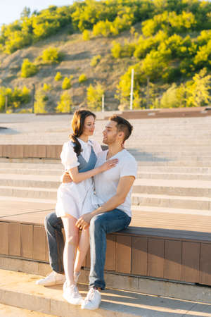 Full length vertical portrait of happy young couple resting in city park sitting on bench in summer sunny day. Relationships between cheerful boyfriend and girlfriend enjoying time together outdoors. Stock fotó