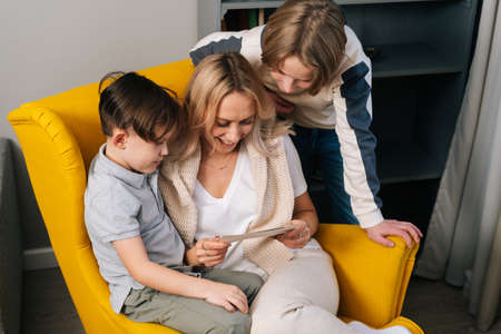 Close-up top view of two child sons and happy mum reading surprise handmade gift card sitting in armchair in cozy living room. Cheerful young woman smiling and reading greeting card to happy boy.