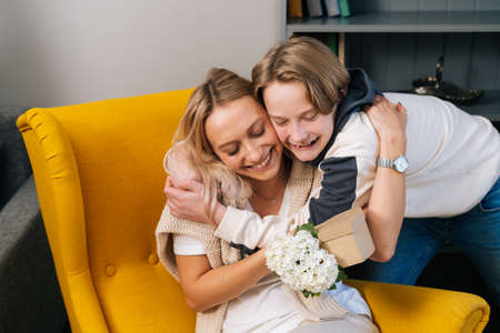 Middle shot portrait of smiling loving kid son hugging kissing happy young mom congratulating with mothers day. Cheerful young woman receiving gift from son. Concept of family holidays celebration.