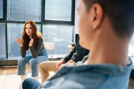 Back view of sad crying young woman sharing mental problem to other patients sitting in circle during group therapy session. Concept of group consulting of mental health problem with psychologist.