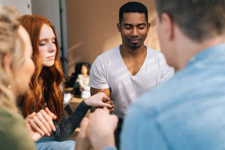 Group of young diverse multiethnic people holding hands together during the psychological therapy, meditating and solving together mental problems. Concept of group consulting of mental health problem Stock fotó