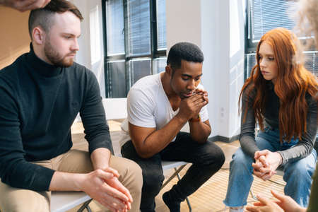 Close-up of depressed African American young man sharing problem sitting in circle on group therapy session. Concept of group consulting of mental health problem with professional psychologist. Stock fotó