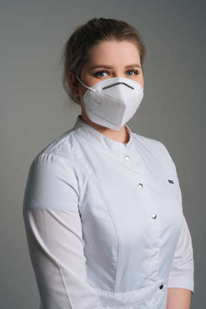 Vertical portrait of young female doctor wearing medical coat and protective face mask standing on dark isolated background. Studio shot of nurse posing with crossed arms looking at camera.