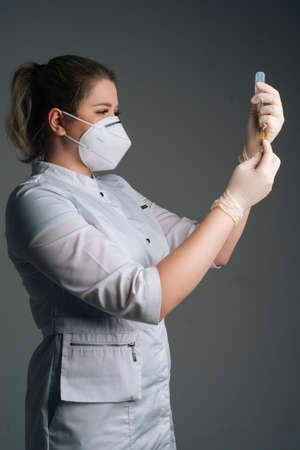 Veretical studio shot of nurse in white gloves and face mask holding and filling up vaccine to syringe on black isolated background. Doctor preparing to give injection of coronavirus vaccine. Stock fotó